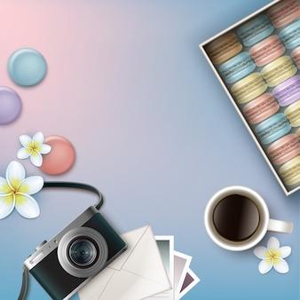 Vector doos met kleurrijke franse macarons met koffie, plumeria bloemen, fotocamera, envelop en kaarten op roze blauwe achtergrond bovenaanzicht