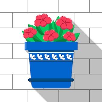 Vector kleurrijke plant in de blauwe pot op lichte bakstenen muur achtergrond rode bloemen en groene bladeren