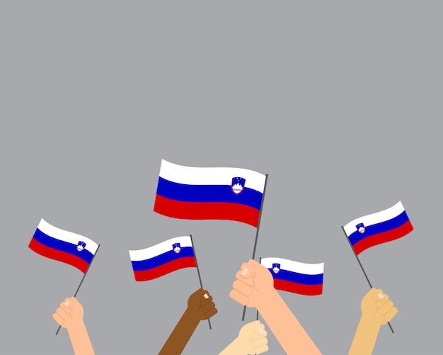 Vectorillustratie van handen die de vlaggen van slovenië houden