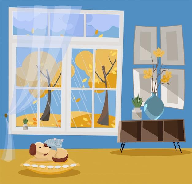 Venster met uitzicht op gele bomen en vliegende bladeren. herfst interieur met slapende kat en hond. regenachtig weer buiten.