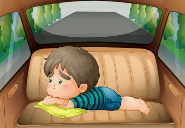 Verdrietig jongetje achter in de auto