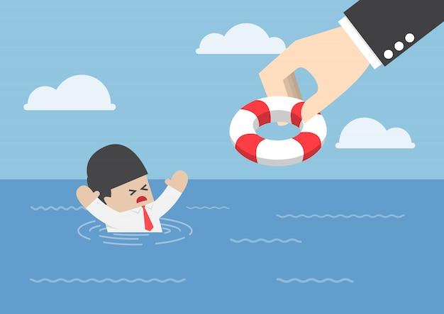 Verdrinkende zakenman die reddingsboei van grote hand krijgen