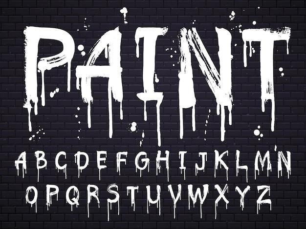 Verf druipende verf lettertype voor latijnse alfabet geïsoleerd op zwarte bakstenen muur