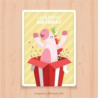 Verjaardagskaart met een eenhoorn die uit een cadeau komt
