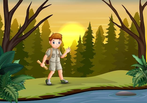 Verkennerjongen die het bos met zijn kaarten onderzoekt