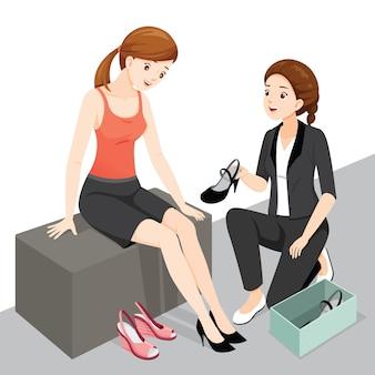 Verkoopster die vrouwklant in de winkel van damesschoenen zeer goed onderhoudt