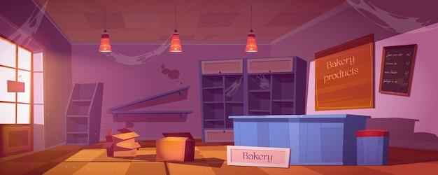 Verlaten bakkerij, leeg verwaarloosd bakhuisinterieur met gebroken planken, vuile krijtmenubord en spinnenwebben en dozen op vloer.