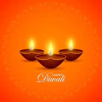 Verlichte olielampen (diya) op oranje achtergrond voor gelukkige diwali-viering