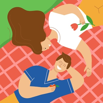 Verliefde paar met een picknick in het park een man en een vrouw liggen op een plaid en lachen