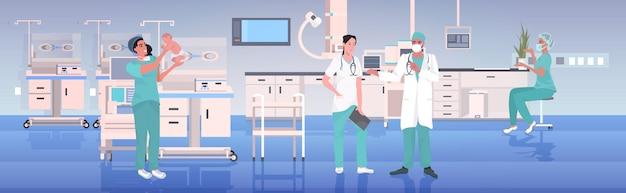 Verloskundige in uniform houden pasgeboren baby artsen team samenwerken geneeskunde gezondheidszorg verloskundige concept moderne ziekenhuis kliniek interieur volledige lengte horizontaal