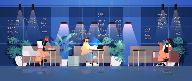 Vermoeide zakenmensen werken samen in creatief coworking center teamwork concept donkere nacht kantoor interieur horizontaal volledige lengte