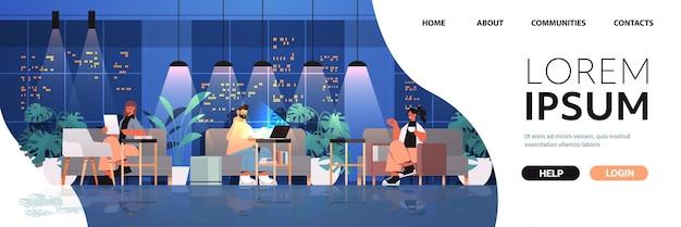Vermoeide zakenmensen werken samen in creatieve coworking center teamwork concept donkere nacht kantoor interieur horizontale volledige lengte kopie ruimte