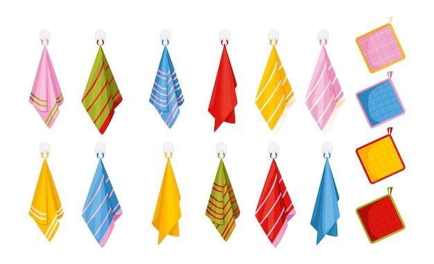 Verzameling van geïsoleerde keukenelementen met handdoeken van verschillende kleuren die aan haken hangen met pannenlappen