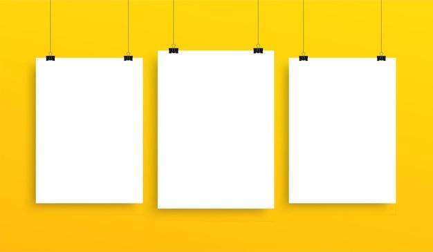 Verzameling van verticaal hangend postermodel, witte blanco vellensjabloon op gele muur