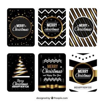 Verzameling van zes kerstkaarten in zwart met gouden en witte elementen
