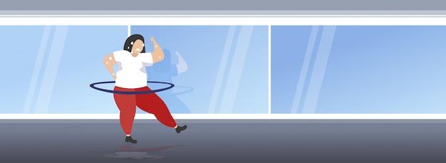 Vet zwaarlijvig meisje draaien hoelahoep overgewicht zweet vrouw cardiotraining training gewichtsverlies concept volledige lengte moderne sportschool studio interieur horizontaal