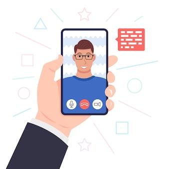 Video-oproep. hand met smartphone. jonge man met bril op het scherm. .