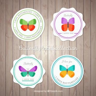 Vier badges met vlinders op een houten achtergrond
