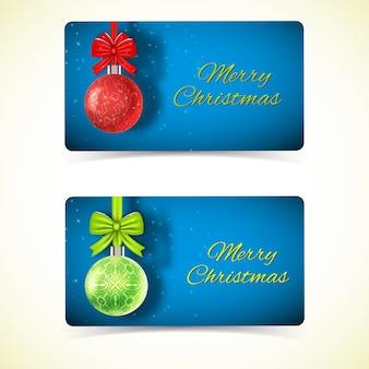 Vieren horizontale wenskaarten met hangende rode en groene kerstballen op blauw