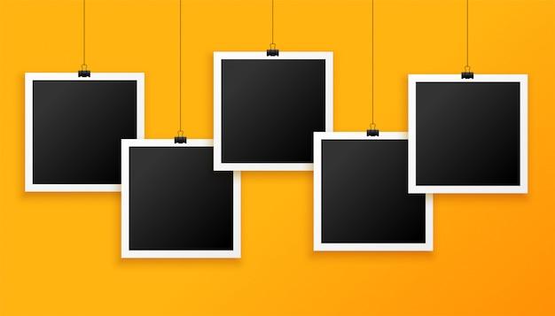 Vijf hangende fotoframes op gele achtergrond