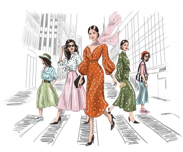 Vijf vrouwen die op een zebrapad in grote stad lopen