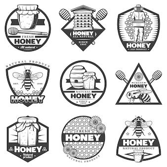 Vintage monochrome honingetiketten instellen met bijenkorf imker stokken bijen bloemen potten honingraten geïsoleerd