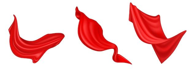 Vliegende rode zijde stof geïsoleerd op een witte achtergrond. realistische set golvende fluwelen kleding, gordijnen of sjaal in de wind. luxe rode stoffen draperie, vloeiende satijnen stof