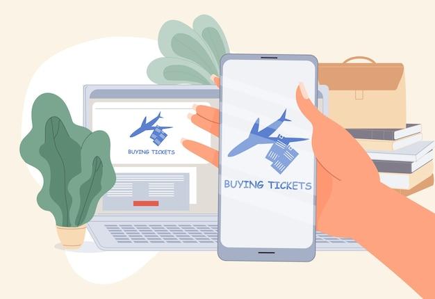 Vliegticket online kopen. computerservice, mobiele telefoontoepassing voor het eenvoudig boeken van een zakenreisvlucht. menselijke hand houdt smarpton vast. laptop, boekenstapel op tafel. reserveren op afstand