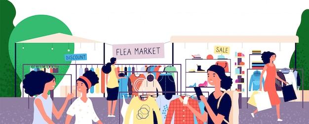 Vlooienmarkt. vrouwenkopers die modekleding bij bazaar kiezen.