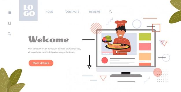 Voedsel blogger in uniform koken pizza mannelijke chef-kok opname video blog live streaming blogging concept man vlogger uitleggen hoe een schotel te koken monitor scherm horizontaal exemplaar ruimte portret