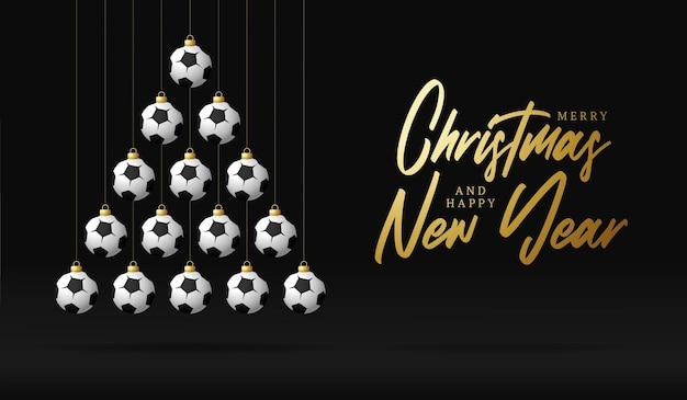 Voetbal kerstmis en nieuwjaar wenskaart snuisterij boom. creatieve kerstboom gemaakt door voetbal bal op zwarte achtergrond voor kerstmis en nieuwjaar viering. sportwenskaart