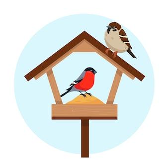 Vogelvoederhuis en twee vogels bij koud weer hongerige mus en goudvink in de voederbak