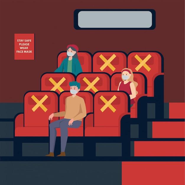 Volkeren kijken naar films in het theater terwijl ze afstand houden en een medisch masker gebruiken
