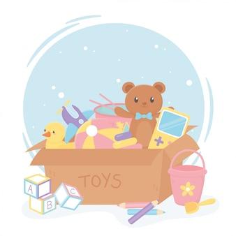 Volle kartonnen doos met cartoon kinderspeelgoed beer eend emmer blokken bal vliegtuig potloden