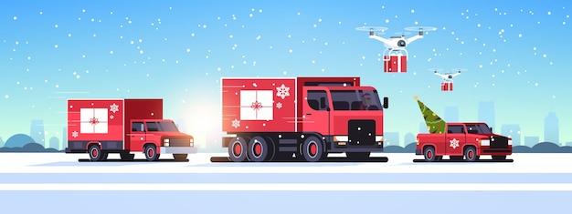 Vrachtwagens pick-up auto rijden weg quadcopters met geschenkdozen levering verzending vervoer vrolijk kerst winter vakantie concept horizontaal besneeuwd stadsgezicht vector illustratie