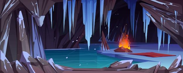 Vreugdevuur in donkere ijsgrot met sneeuw, bevroren water en ijzige kristallen.