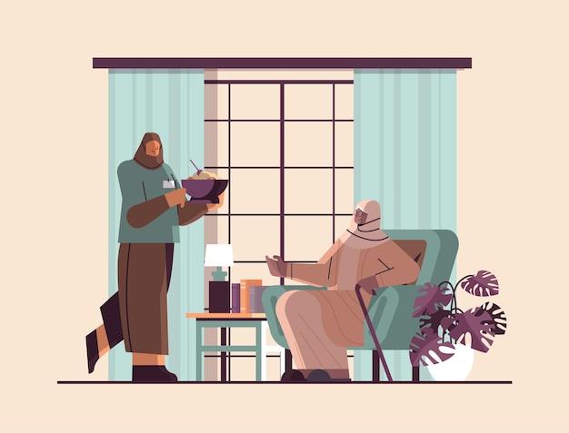 Vriendelijke arabische verpleegster of vrijwilliger die eten brengt bij thuiszorg voor bejaarden, gezondheidszorg en sociale ondersteuning