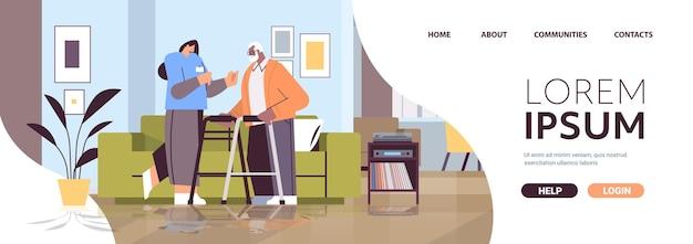 Vriendelijke verpleegster of vrijwilliger die afro-amerikaanse oudere man ondersteunt met wandelaars thuiszorgdiensten gezondheidszorg en sociale ondersteuning concept horizontale volledige lengte kopieerruimte