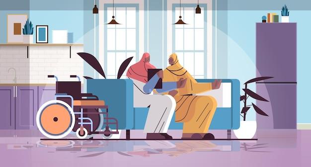 Vriendelijke verpleegster of vrijwilliger die arabische bejaarde vrouw thuiszorgdiensten ondersteunt, gezondheidszorg en sociaal ondersteuningsconcept