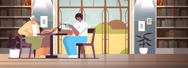 Vriendelijke verpleegster of vrijwilliger die de bloeddruk controleert bij oudere vrouw patiënt thuiszorg diensten gezondheidszorg en sociale ondersteuning concept verpleeghuis interieur horizontaal volledige lengte
