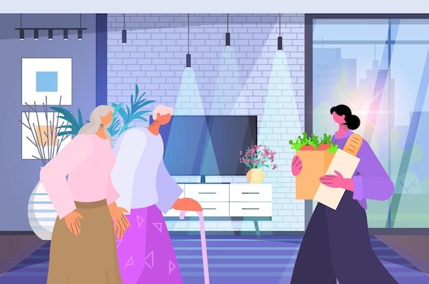 Vriendelijke verpleegster of vrijwilliger die eten brengt aan senior koppel thuiszorgdiensten gezondheidszorg en sociale ondersteuning concept