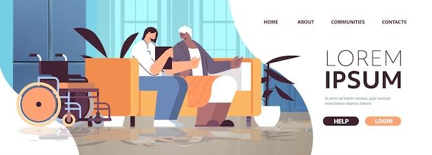 Vriendelijke verpleegster of vrijwilliger ter ondersteuning van afro-amerikaanse bejaarde vrouw thuiszorgdiensten gezondheidszorg en sociale ondersteuning concept verpleeghuis interieur horizontale kopieerruimte volledige lengte