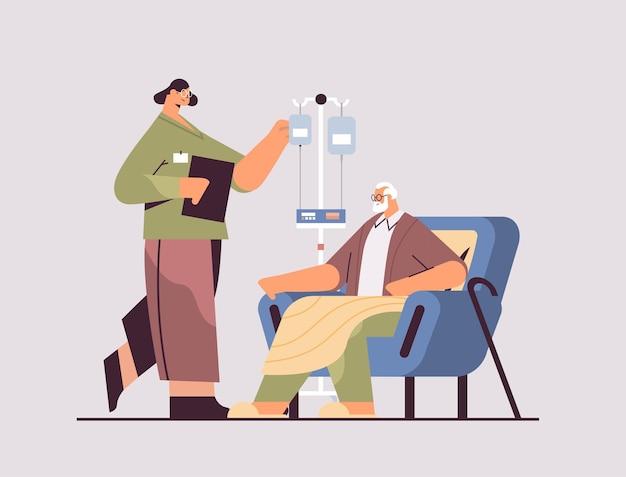 Vriendelijke vrouwelijke verpleegster of vrijwilliger die de druppelaar van de bejaarde patiënt controleert thuiszorgdiensten gezondheidszorg en sociale ondersteuning concept horizontaal volledige lengte