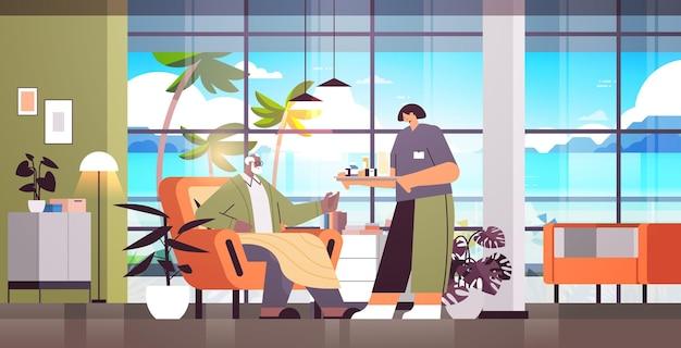 Vriendelijke vrouwelijke verpleegster of vrijwilliger die pillen brengt naar afro-amerikaanse bejaarde man thuiszorgdiensten gezondheidszorg en sociale ondersteuning concept horizontaal volledige lengte