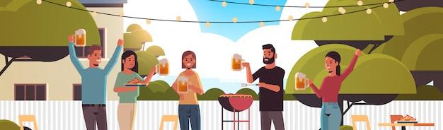 Vrienden die hotdogs bij de grill voorbereiden en bier drinken gelukkige mannen vrouwengroep die pretbinnenplaats hebben picknickbarbecue partijconcept vlak portret horizontaal