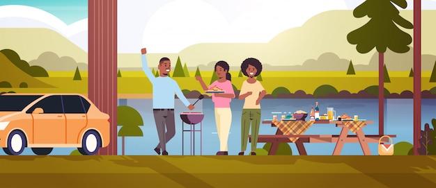Vrienden die hotdogs op de grill afrikaanse amerikaanse man voorbereiden en vrouwen die van de de barbecuepartij van de pretpicknick het park of het landschap van de rivierbank vlakke volledige horizontale lengte hebben als achtergrond