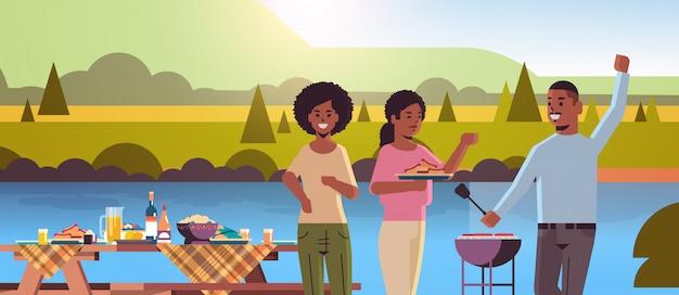 Vrienden die hotdogs op grill afrikaanse amerikaanse man voorbereiden en vrouwen die van de de barbecuepartij van de pretpicknick het park of het landschapslandschap van de rivierbank vlak horizontaal portret hebben als achtergrond
