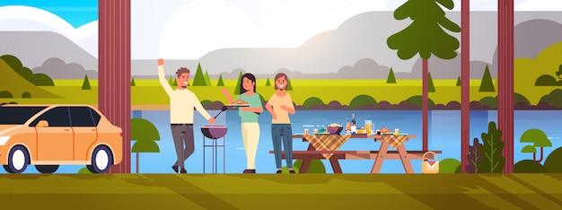 Vrienden die hotdogs op grill gelukkige man voorbereiden en vrouwen die van de de barbecuepartij van de pretpicknick het conceptenpark of het landschap van de rivierbank vlakke volledige horizontale lengte hebben als achtergrond