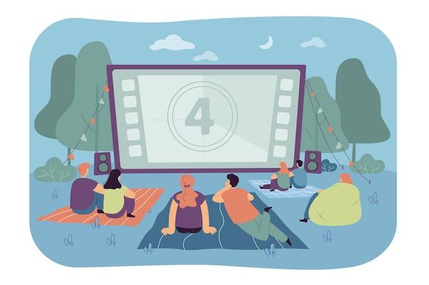 Vrienden kijken naar film in openluchtbioscoop