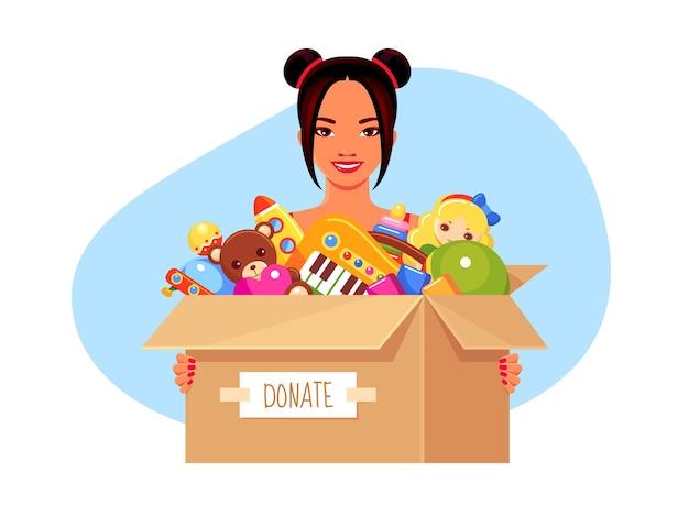 Vrijwilliger aziatisch lachend meisje met donatiepapieren doos met kinderspeelgoed